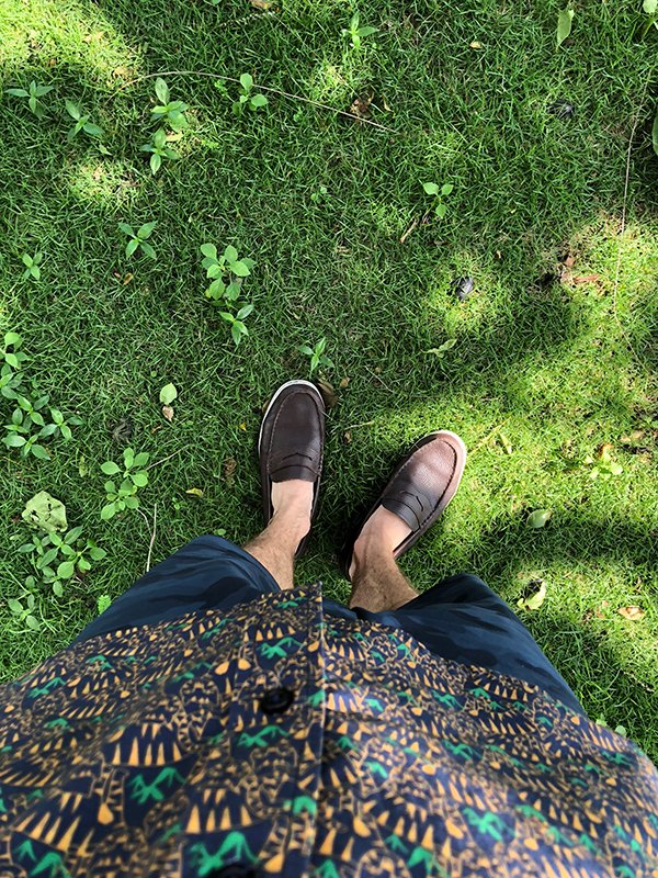 A first person view of a man looking down at the mossy floor while wearing a casual button down shirt with an all over cats print and brown loafers