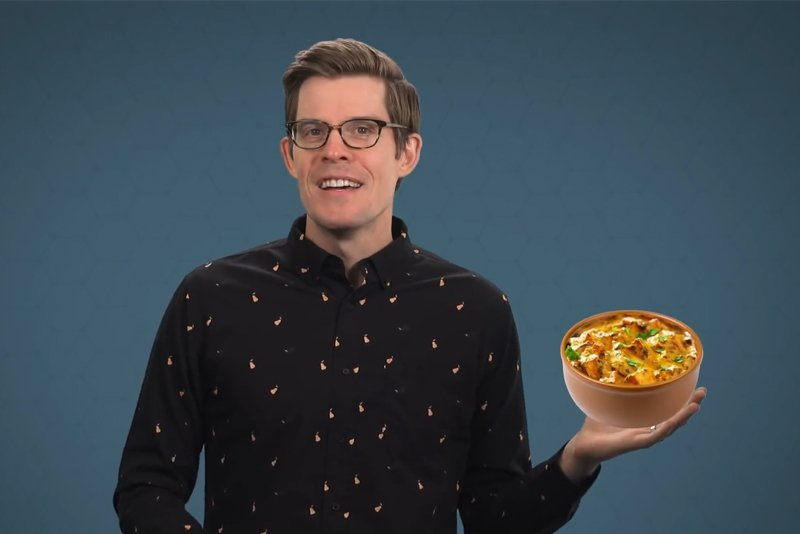 Joe Hanson wearing a pears casual button down printed shirt while holding a bowl of chilli