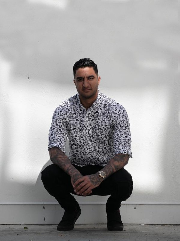 A handsome young man with arm tattoos wearing a monochrome floral casual button down shirt while crouching