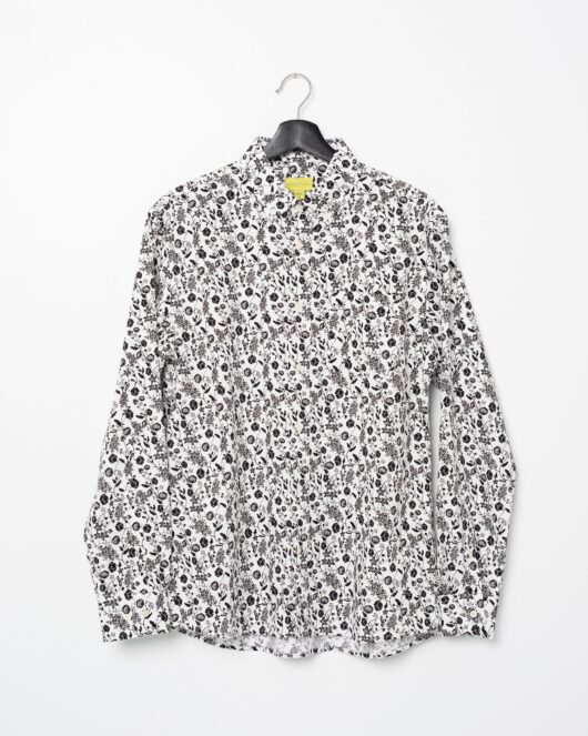A product flat of a floral white and black casual button down long sleeve shirt covered with flowers