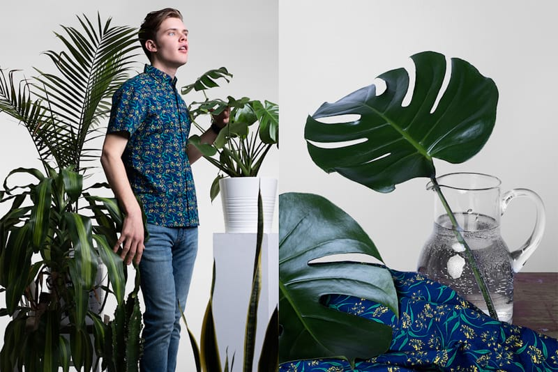 Banner depicting a young man standing in between potted tropical plants while wearing a casual button down floral shirt