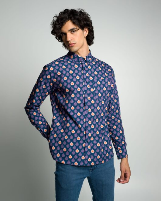A blue and purple casual button down long sleeve shirt covered with abstract figs worn by a handsome young man in blue jeans
