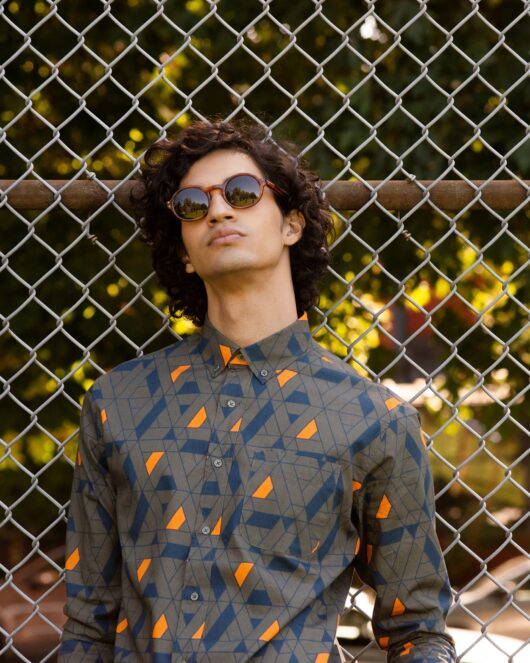 A green casual button down long sleeve shirt with an all over blue and orange geometric print worn by a handsome young man leaning against a chain link fence
