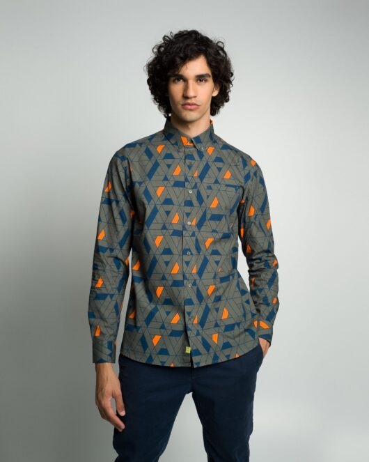 A green casual button down long sleeve shirt with an all over blue and orange geometric print worn by a handsome young man in blue joggers