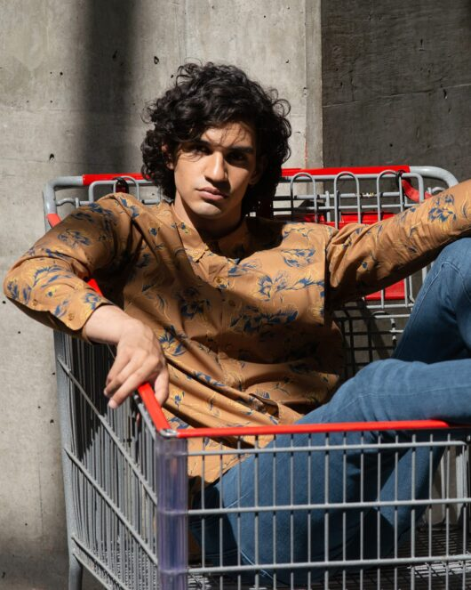 A floral brown and navy casual button down long sleeve shirt with an all over large floral print worn by a handsome young man sitting in a shipping cart