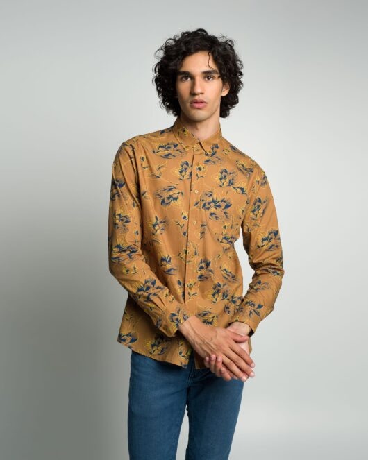 A floral brown and navy casual button down long sleeve shirt with an all over large floral print worn by a handsome young man in blue jeans