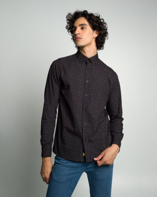 A black casual button down long sleeve shirt with an all over polka dot print worn by a handsome young man in blue jeans