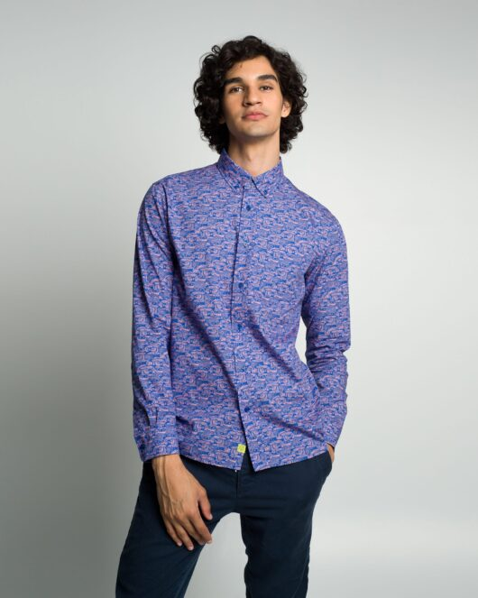A blue and pink casual button down long sleeve shirt with an all over owl print worn by a handsome young man in blue joggers