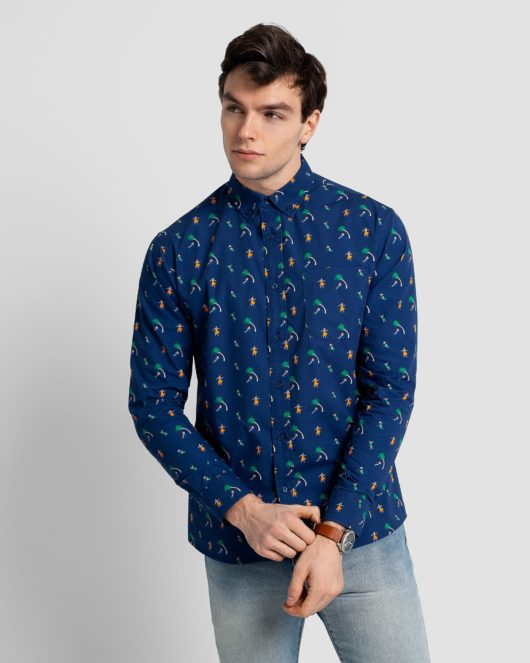 A blue casual button down long sleeve shirt with an all over hawaiian print worn by a handsome young man in light blue jeans