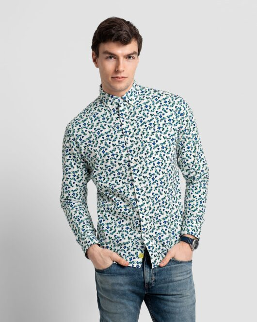 A white and blue casual button down long sleeve shirt with an all over blueberry print worn by a handsome young man in light blue jeans