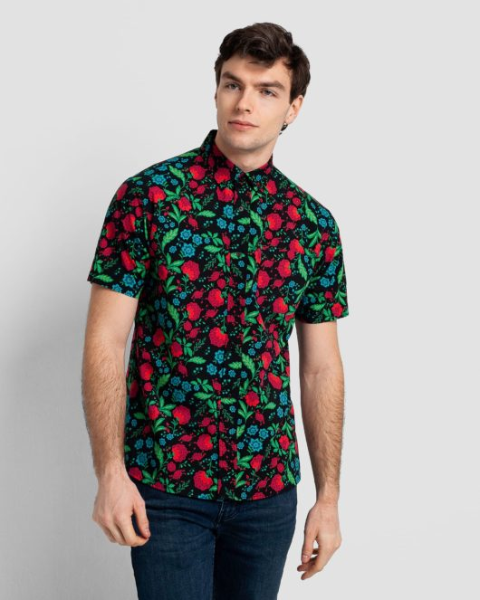 A hawaiian casual button down short sleeve shirt covered with red, blue and green flowers worn by a handsome young man in dark blue jeans