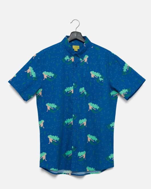 A product flat of a blue and green casual button down short sleeve shirt with a mermaids and seahorses printed on it