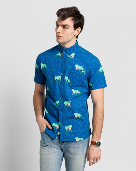 A Casual Button Down Short Sleeve Shirt with a Mermaids and Seahorses Print being worn by a handsome young man wearing jeans and a Fossil watch